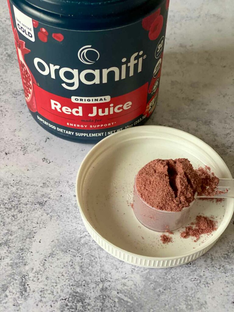 organifi red juice powder in jar with a scoop out shown on lid
