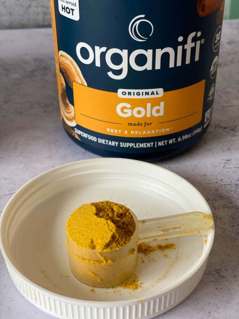 organifi gold juice powder in tub with a scoop out shown on lid