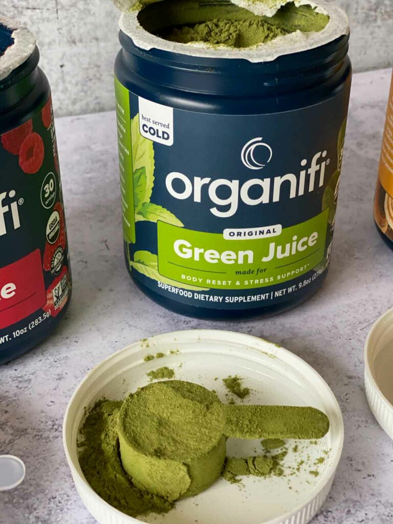 organifi green juice powder in jar with a scoop out shown on lid