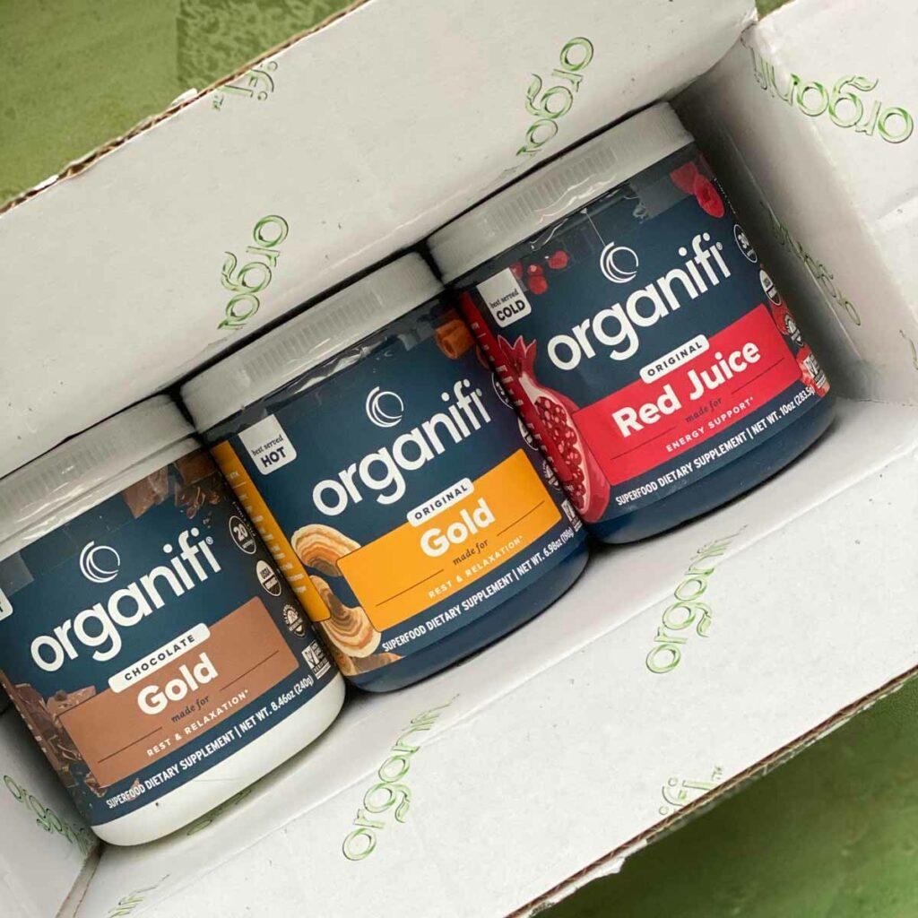 3 jars of organifi powder in box, chocolate gold, original gold, red juice