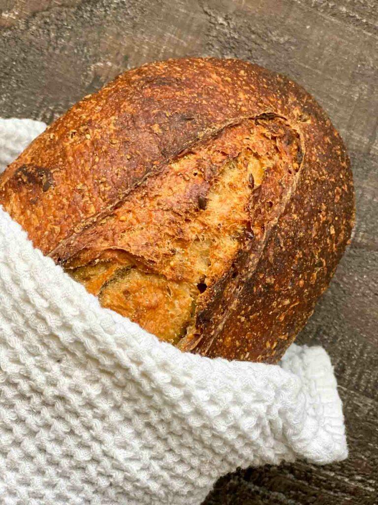Wildgrain loaf of 7-grain sourdough bread after baking, wrapped in tea towel