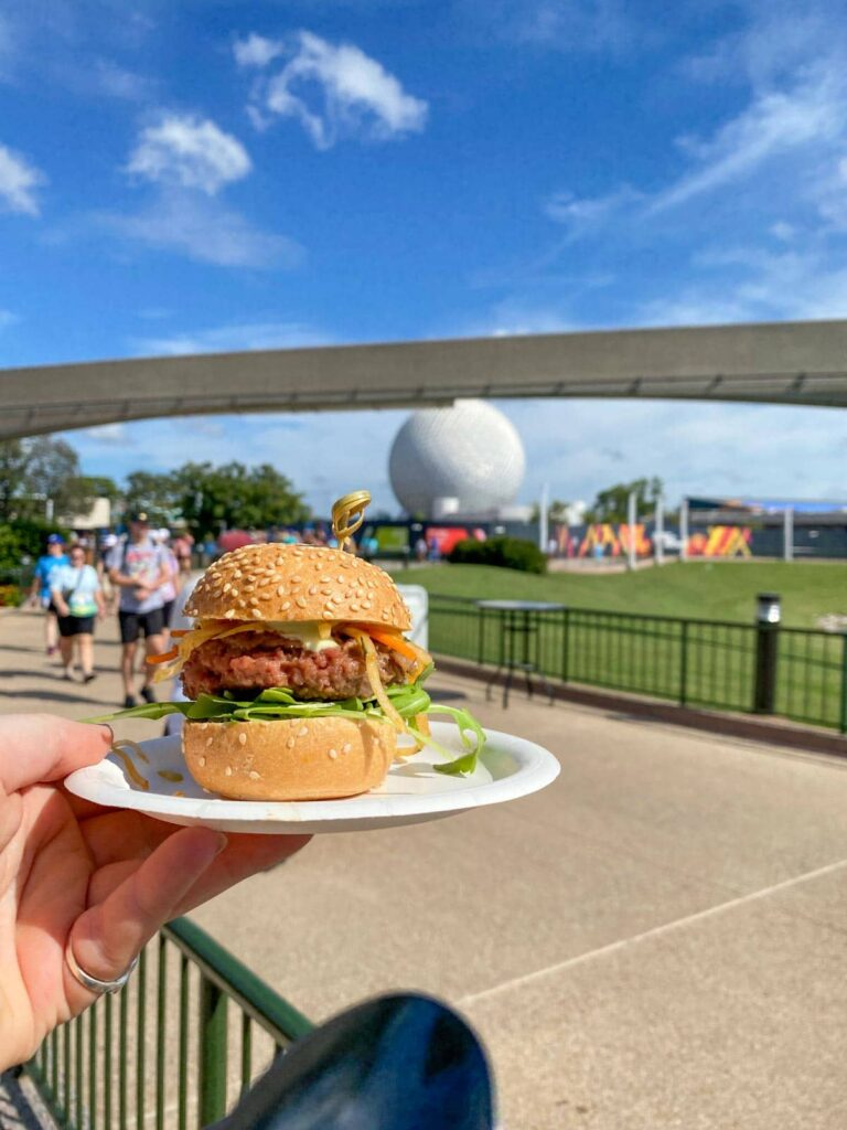 Earth Eats impossible burger slider held up against the Epcot globe